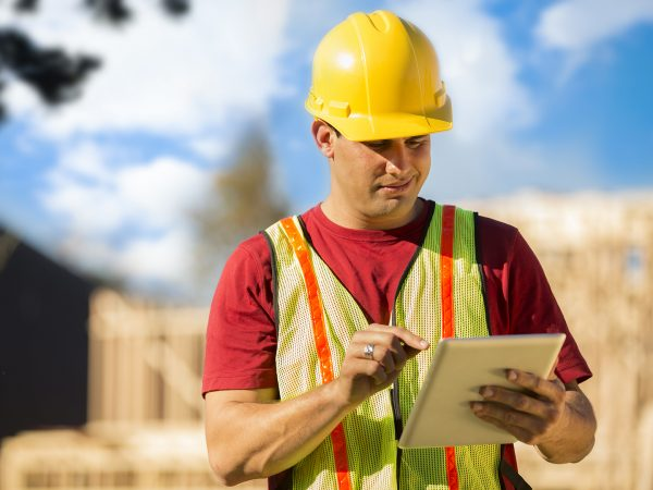 A Latin descent construction worker, supervisor, contractor, inspector, architect, or engineer inspects the work at a construction site.  Framed house, building in background.  He is wearing a hard hat and safety vest and is using his digital tablet.